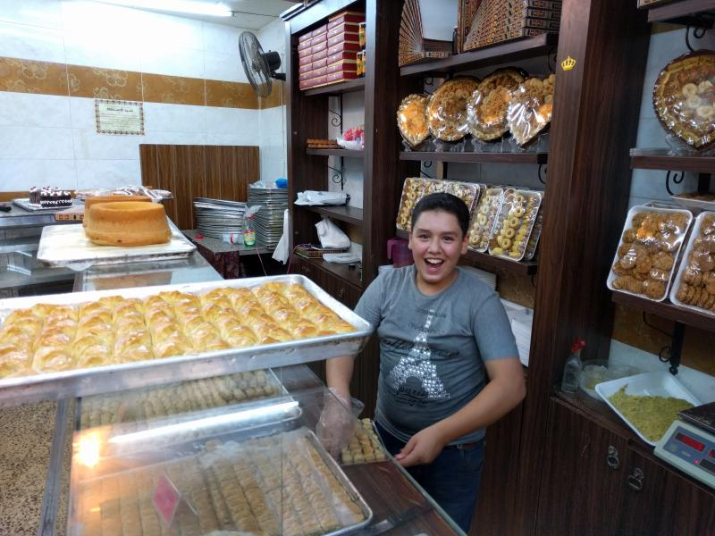 Young child smiling and wrapping up baklava in a shop in Amman