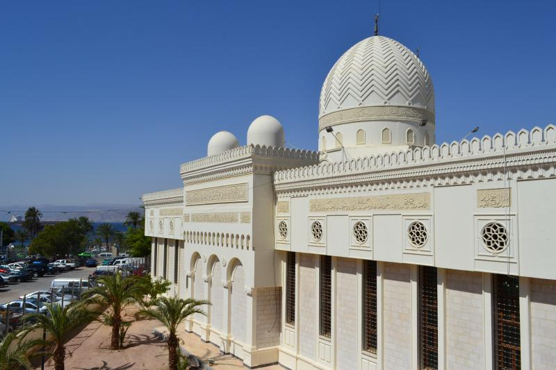 Beautiful mosque by the sea, surrounded by palm trees