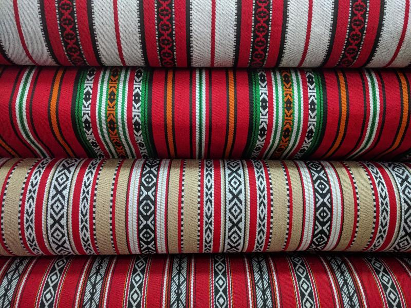 Several reams of colorful fabric stacked vertically in a shop in downtown Amman.