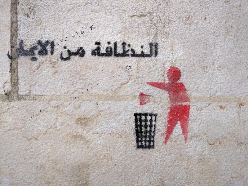 Graffiti with Arabic inscription depicting someone putting trash in a trash can