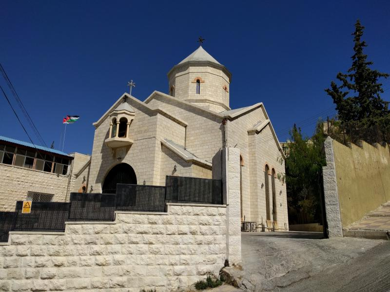 Armenian church with pointy blue steeple in traditional style